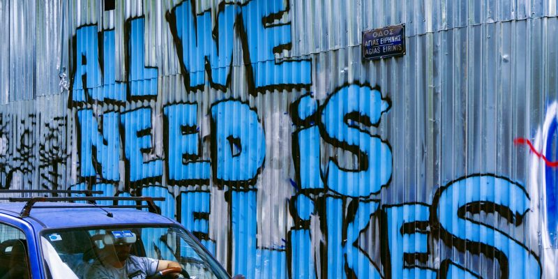 Graffiti saying All We Need Is Likes on corrugated iron fence